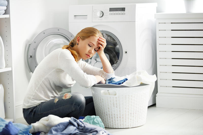 Tired unhappy woman housewife fold clothes into the washing mac royalty free stock photography