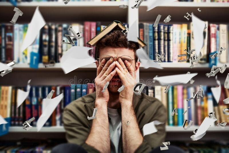 Tired university student has difficulty to study. Concept of stress and difficulty stock image