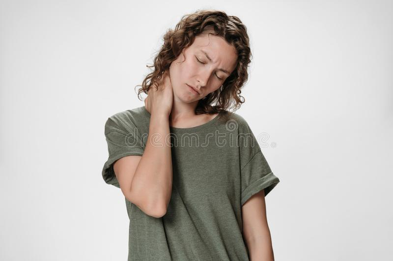 Tired upset young caucasion woman suffering from fatigued massaging hurt stiff neck stock photography