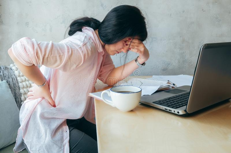 Tired upset young businesswoman suffering from strong chronic backache or osteochondrosis at work, stressed student girl feels royalty free stock images
