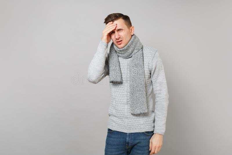 Tired upset young man in gray sweater, scarf having headache, put hand on head on grey wall background. Healthy royalty free stock photos