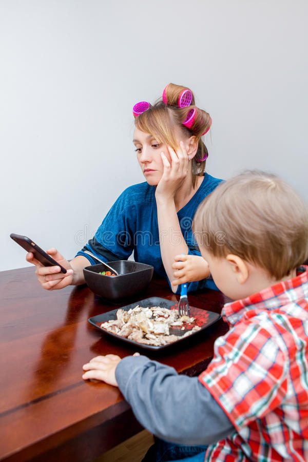Tired white Caucasian young woman mother housewife with hair-curlers in hair looking on phone surfing Internet royalty free stock photo