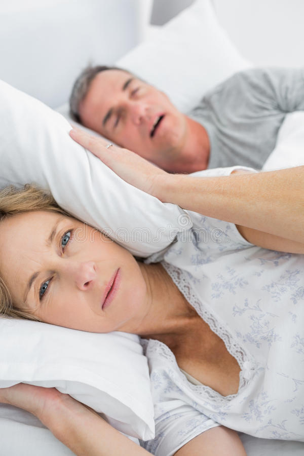 Tired Wife Blocking Her Ears From Noise Of Husband Snoring Looking At Camera Royalty Free Stock Image