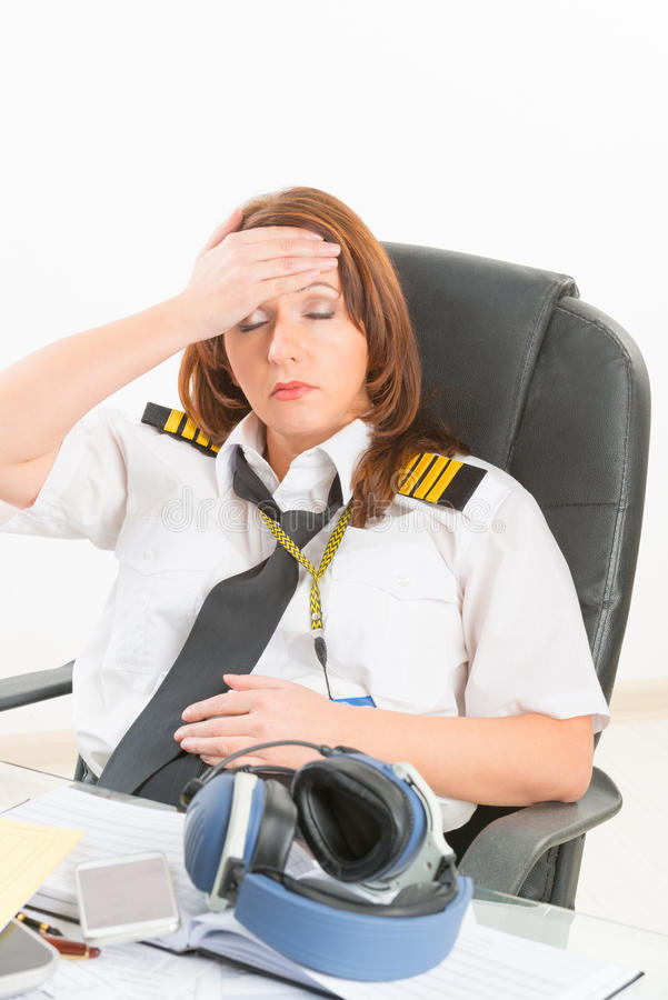 Tired woman airline pilot in the office. Overworked tired woman pilot wearing uniform with epaulettes resting or sleeping in briefing room stock photo