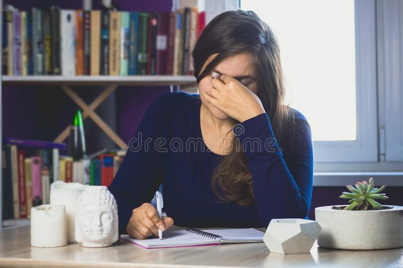 Tired woman with arm rubs his eyes sitting at the table. In the background of the bookcase royalty free stock image