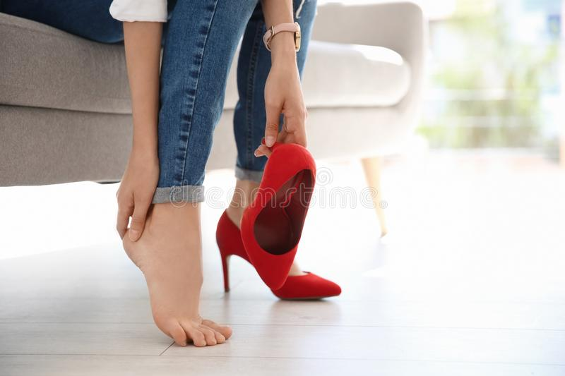 Tired woman with beautiful legs taking off shoes royalty free stock photography