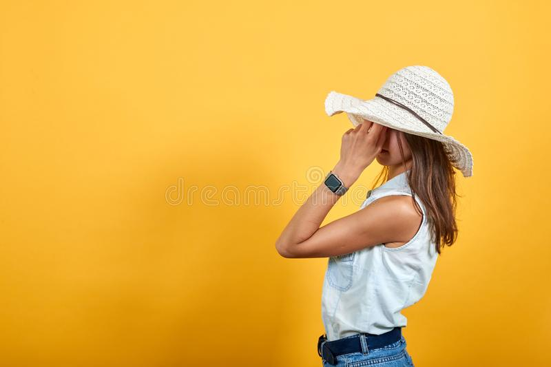 Tired woman in blue denim shirt and nice hat keeping hand on head stock images