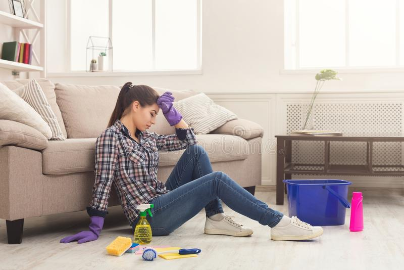 Tired woman cleaning house with lots of tools. Young exhausted girl sleeping at home near detergents, copy space royalty free stock photo