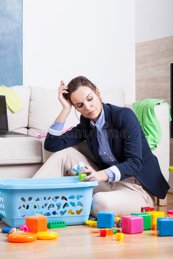 Tired woman cleaning up room from toys. Tired woman cleaning up room from kids toys stock photo