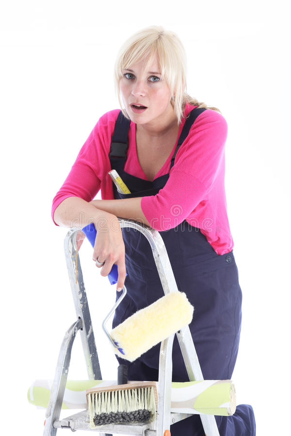 Tired woman doing wallpapering. Tired woman flopped over the top of the ladder taking a break from doing wallpapering and redecorating in her home stock photo