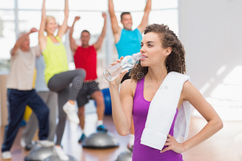 Tired woman drinking water at fitness club stock images
