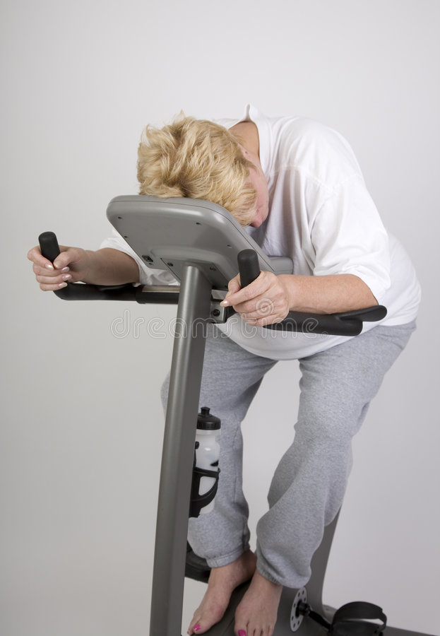 Tired woman on excercise bike royalty free stock photography