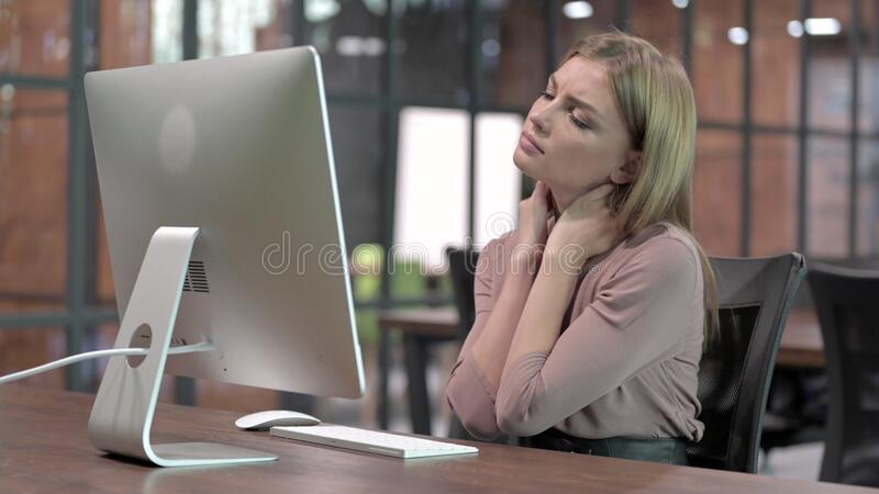 Tired Woman having Neck Pain while Working on Computer stock photography