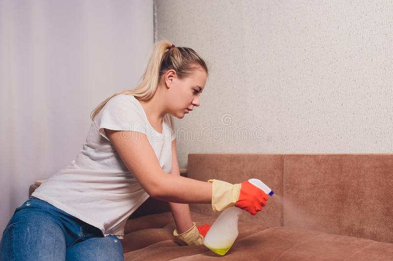 Tired woman having rest after cleaning home, lying on sofa in the living-room, copy space. Housekeeping and home stock photo