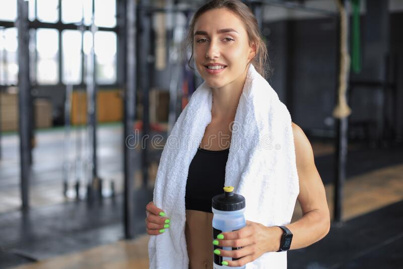 Tired woman having rest after workout. Exhausted female athlete at gym with towel around her neck.  stock photo