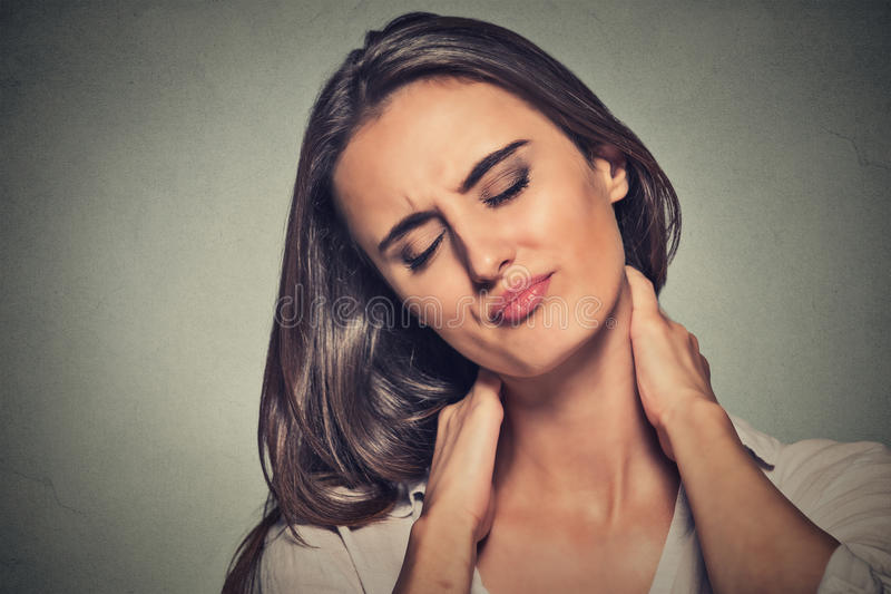 Tired woman massaging her painful neck royalty free stock photo
