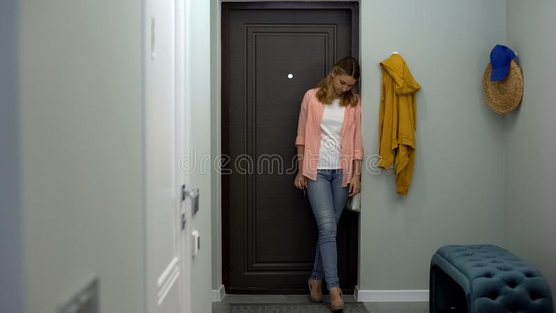 Tired woman opening door and entering apartment, exhausted after work, lonely stock image