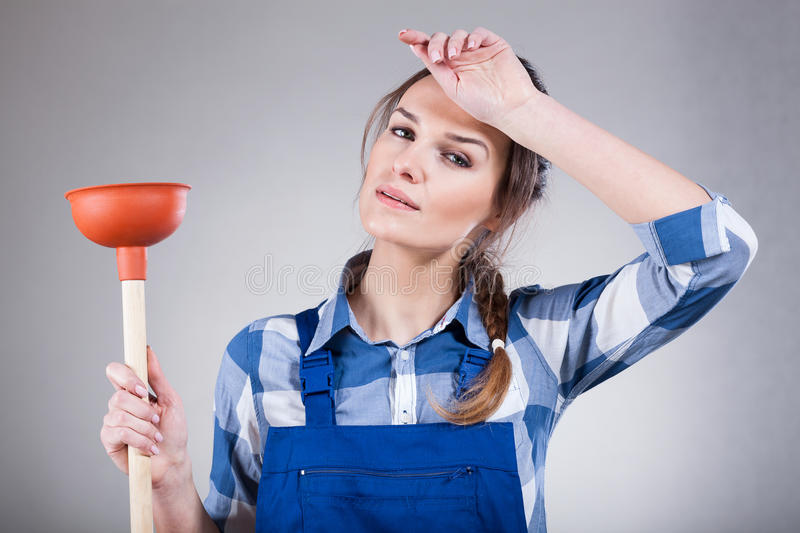 Tired woman with a plunger. Tired, young woman with a plunger, horizontal stock image