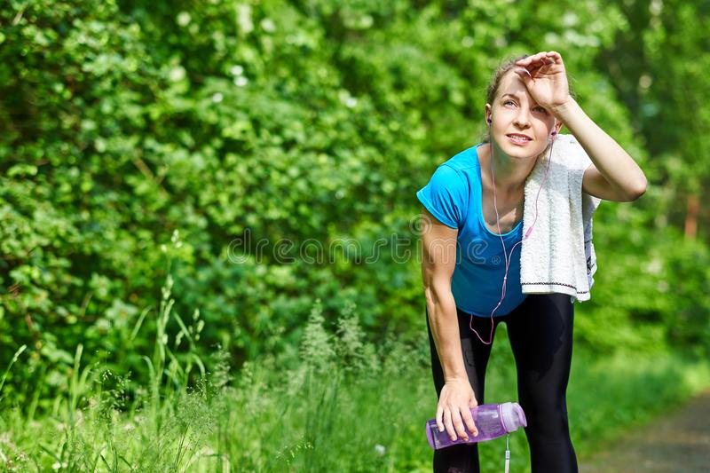 Tired woman runner having rest after running hard on road in forest, bending forward, resting elbows on her knees stock photos