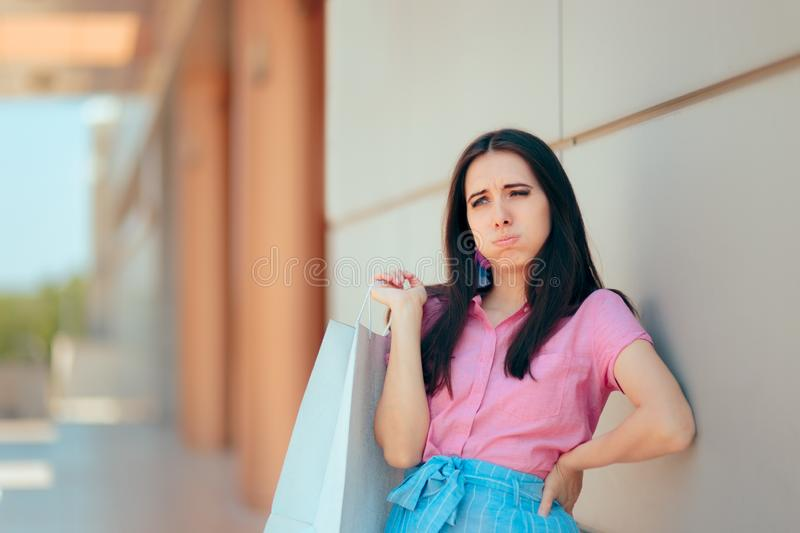 Tired Woman After Shopping Session at the Mall. Shopper girl in pain feeling her spine injured after carrying many bags royalty free stock images