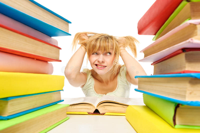 Download Tired Woman Sitting At The Desk Surrounded With Piles Of Books Stock Photo - Image: 28654586