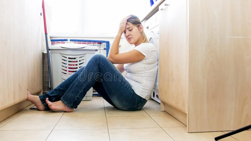 Tired young woman sitting on floor at laundry room. Tired woman sitting on floor at laundry room royalty free stock photos