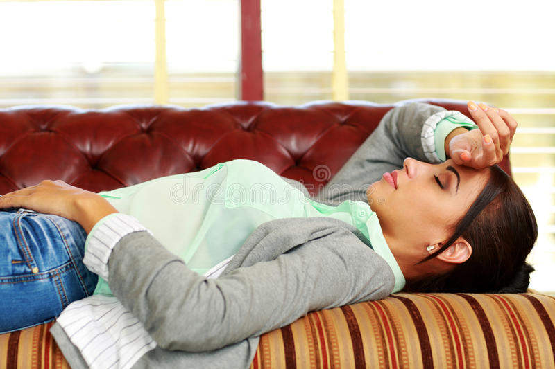 Tired woman sleeping on the coach royalty free stock photography