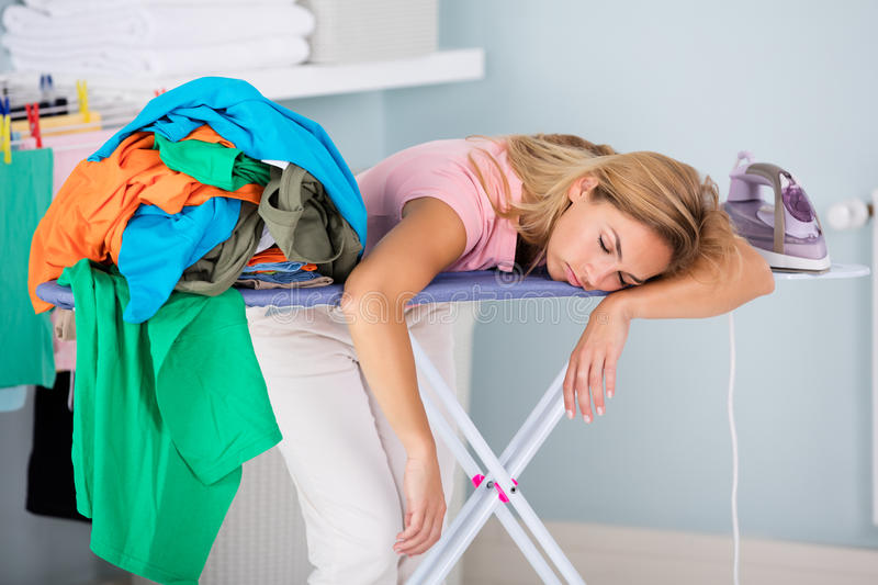 Tired Woman Sleeping On Ironing Board. Young Fatigue Woman Sleeping On Ironing Board Next To Piles Of Clothes At Home royalty free stock photos