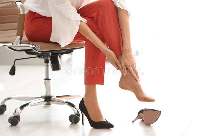 Tired woman taking off shoes at office stock photography