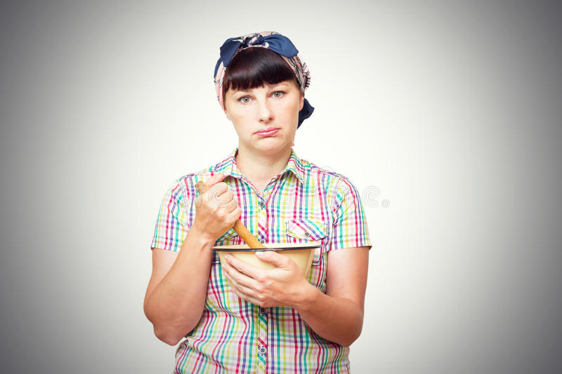 Tired woman with utensils in hand on white background. stock images