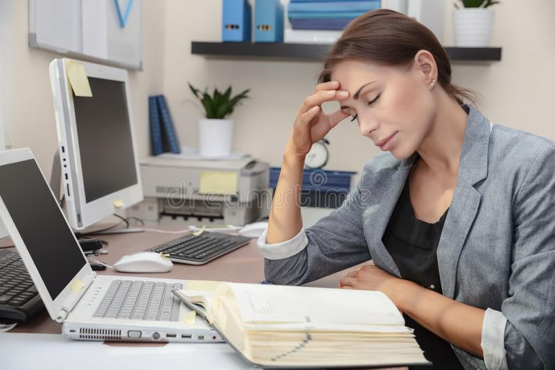 Tired woman at work royalty free stock photography