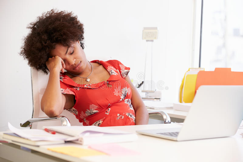 Tired Woman Working At Desk In Design Studio stock photos