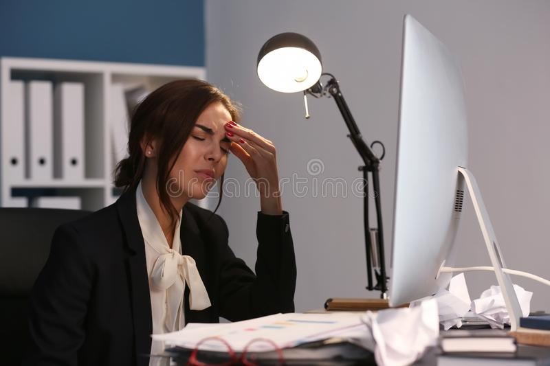 Tired woman working late in evening royalty free stock photography