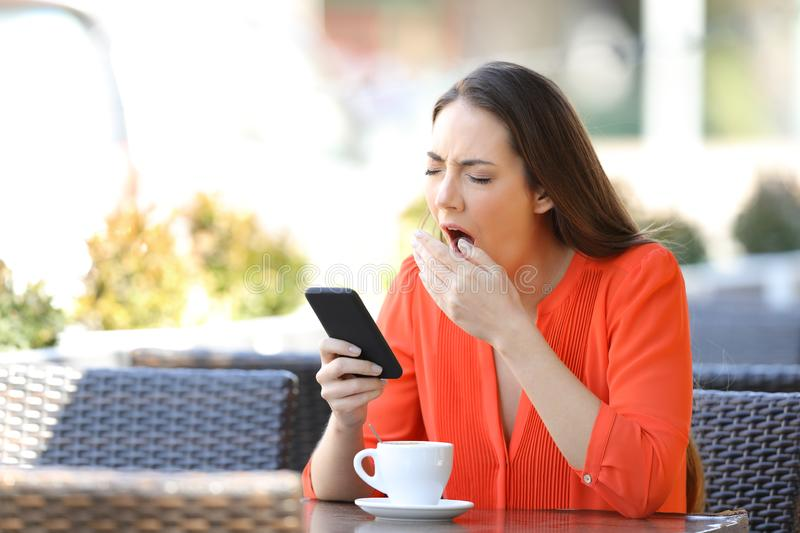 Tired woman yawning holding phone in a bar stock photo