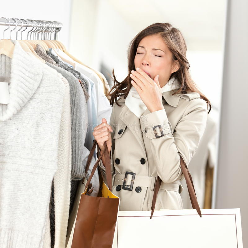 Tired woman yawning shopping clothes. Tired woman yawning while shopping clothes in clothing store shop. Beautiful young mixed race Asian / Caucasian female stock image