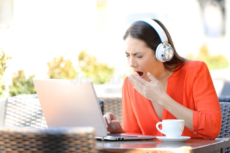 Tired woman yawning using a laptop in a bar royalty free stock images