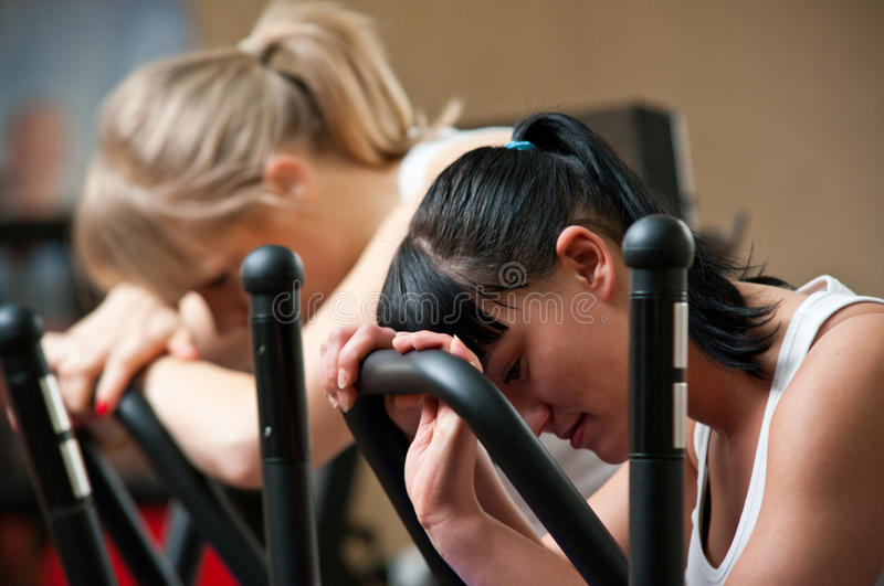 Tired women in gym. Two tired women in a gym, leaning against running machines stock image