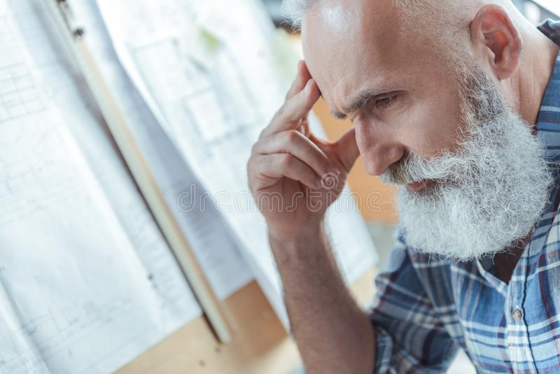 Pensive senior man is feeling exhausted. Tired from work. Close-up of face of old bearded engineer is looking down thoughtfully while touching his head stock image