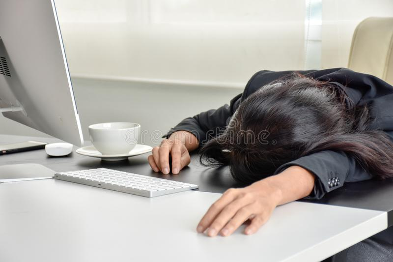 Tired of work. Office girl working hard, sleeping on the desk stock photography