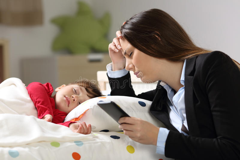 Tired worker mother with her daughter sleeping stock photography