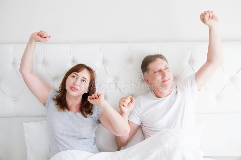 Tired yawn middle age couple in bed. Blank template t shirt. Family life and healthy relationships. Health care and morning royalty free stock photo