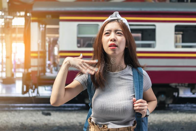 Tired young Asian female feeling so hot at train station. Travel lifestyle concept royalty free stock image
