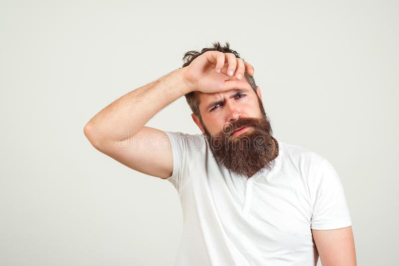 Tired young bearded man on white background. Hand on head. Young handsome bussines man suffering from headache desperate and royalty free stock photography
