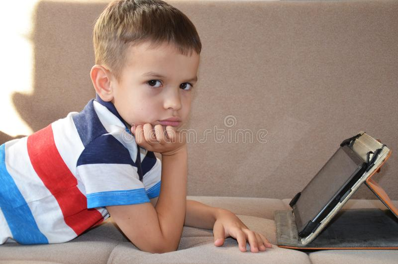 Tired young boy with glasses sitting and holding his head on the tablet in front of the computer, tablet and laptop royalty free stock images