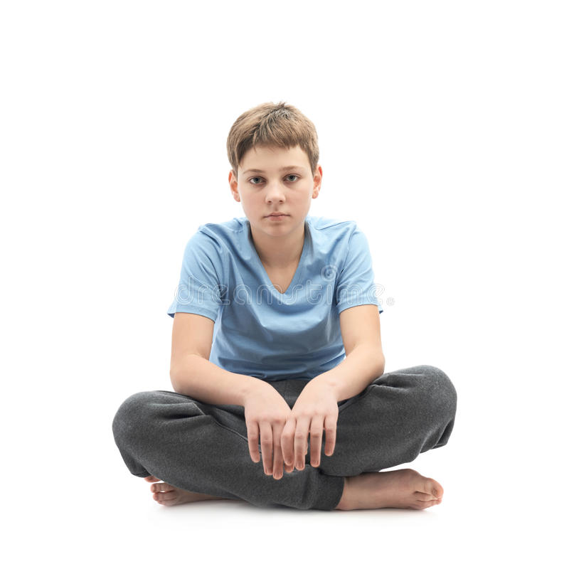 Tired young boy sitting in a lotus position. Tired caucasian 12 years old childen boy in a blue t-shirt sitting in a lotus position, full shot composition royalty free stock photos