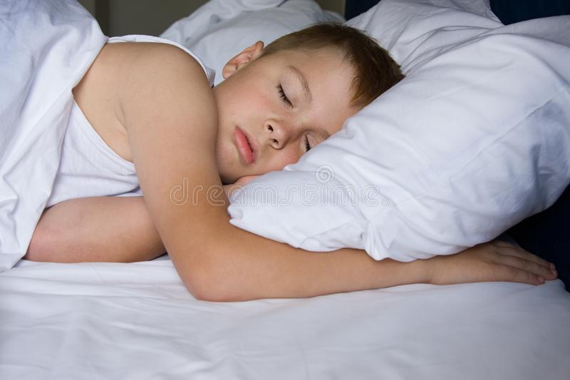 Tired young boy sleeping in bedroom royalty free stock photos