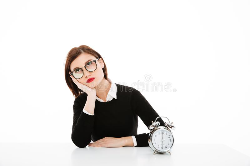 Tired young business lady wearing glasses royalty free stock photography