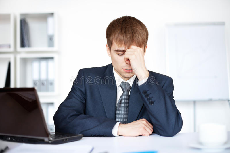 Tired young business man with problems and stress stock photography