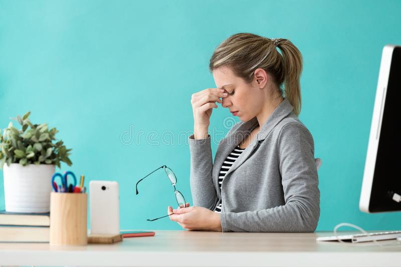 Tired young business woman having headache while working with computer in the office. Shot of tired young business woman having headache while working with stock photo