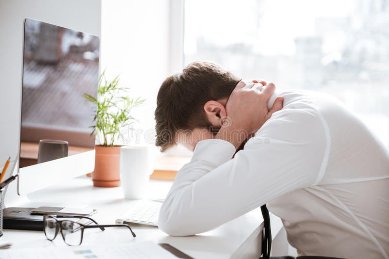 Tired young businessman with painful feelings holding neck. Image of tired young businessman with painful feelings sitting in office while holding his neck stock photos